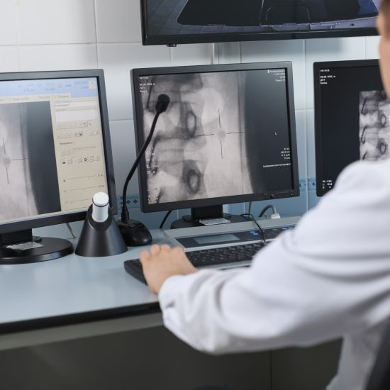 Doctor looking at digital x-rays on a computer monitor
