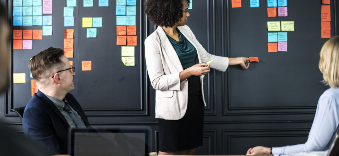 Team Meeting with Woman Placing Sticky Notes on the Wall