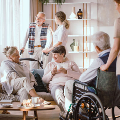 Elderly men and women talking in the common room in nursing home
